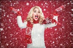 Glückliche lachende blonde Frau kleidete in der Weihnachtsabnutzung mit den Daumen oben, auf rotem Hintergrund haben Kopienraum a Stockfoto