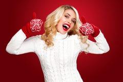 Glückliche lachende blonde Frau kleidete in der Weihnachtsabnutzung mit den Daumen oben an, lokalisiert auf rotem Hintergrund Lizenzfreies Stockbild