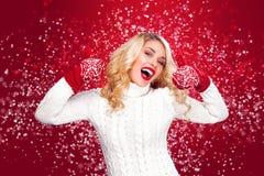 Glückliche lachende blonde Frau kleidete in der Weihnachtsabnutzung mit den Daumen oben an, lokalisiert auf rotem Hintergrund Lizenzfreie Stockfotos