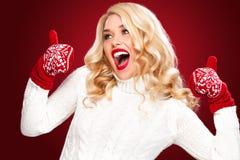 Glückliche lachende blonde Frau kleidete in der Weihnachtsabnutzung mit den Daumen oben an, lokalisiert auf rotem Hintergrund Lizenzfreie Stockbilder