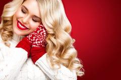 Glückliche lachende blonde Frau kleidete in Weihnachtsabnutzung waitng Geschenken, auf rotem Hintergrund an Stockbild