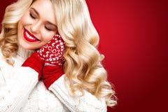 Glückliche lachende blonde Frau kleidete in Weihnachtsabnutzung waitng Geschenken an, lokalisiert auf rotem Hintergrund Lizenzfreies Stockbild