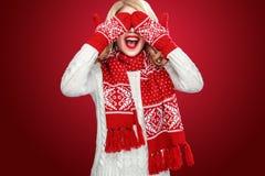 Glückliche lachende blonde Frau kleidete in Weihnachtsabnutzung waitng Geschenken an, lokalisiert auf rotem Hintergrund Stockfoto