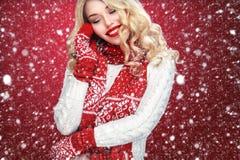 Glückliche lachende blonde Frau kleidete in Weihnachtsabnutzung waitng Geschenken an, lokalisiert auf rotem Hintergrund Stockfotos