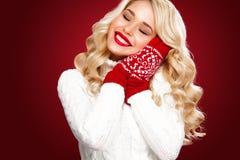 Glückliche lachende blonde Frau kleidete in Weihnachtsabnutzung waitng Geschenken an, lokalisiert auf rotem Hintergrund Stockbild
