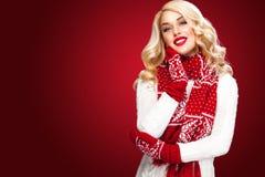 Glückliche lachende blonde Frau kleidete in Weihnachtsabnutzung waitng Geschenken an, lokalisiert auf rotem Hintergrund mit Kopie Stockfotos