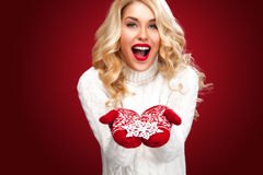 Glückliche lachende blonde Frau kleidete in Weihnachtsabnutzungs-Show snoflake an, lokalisiert auf rotem Hintergrund Stockfotografie
