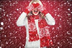 Glückliche lachende blonde Frau kleidete in Weihnachtsabnutzungs-Wartegeschenk, auf rotem Hintergrund mit Schnee an Stockfoto