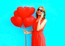 Glückliche lachende Frau des Porträts spricht am Telefon mit Ballonen einer Luft Stockbilder