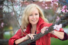 Glückliche lachende kaukasische blonde Frau mit nahem blühendem Pflaumenkirschbaum des langen Haares Stockbild