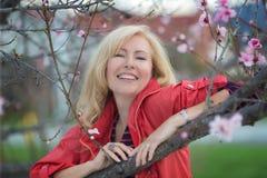 Glückliche lachende kaukasische blonde Frau mit nahem blühendem Pflaumenkirschbaum des langen Haares Lizenzfreie Stockbilder