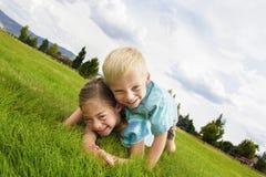 Glückliche lachende Kinder, die draußen spielen Lizenzfreie Stockfotos
