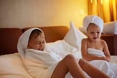 Glückliche lachende Kinder, Junge und Mädchen im weichen Bademantel nach Bad lizenzfreie stockbilder