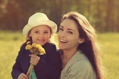 Glückliche lachende Mutter, die ihre Tochter mit gelbem hellem umfasst Lizenzfreies Stockfoto