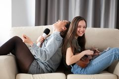 Glückliche lachende Schwestern auf der Couch im Wohnzimmer Stockfotografie