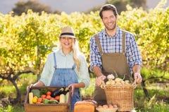 Glückliche Landwirtpaare, die ihr lokales Lebensmittel darstellen Lizenzfreie Stockbilder