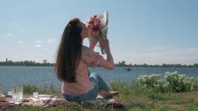 Glückliche langhaarige Frau, die schönen Blumenstrauß in der Natur während des Picknicks auf Rasen durch Fluss im sonnigen Wetter stock video