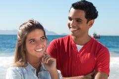 Glückliche lateinische Paare am Strand Stockfoto