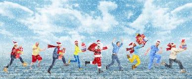 Glückliche laufende Weihnachtsleute stockbild