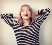 Glückliche laughting blonde Frau mit den geschlossenen Augen, die nahe dem w sich entspannen Stockbild