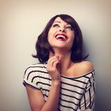 Glückliche laut lachende junge zufällige Frau, die oben schaut Weinlese Clo Stockfotografie