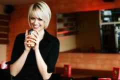 Glückliche lebhafte Frau, die Orangensaft trinkt Lizenzfreies Stockfoto