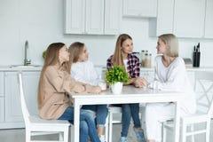 Gl?ckliche lesbische Familie, die zusammen zu Hause in der K?che, alle in der zuf?lligen Kleidung sitzt stockbild