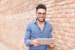 Glückliche Lesung des jungen Mannes auf einem Tablet-Computer Lizenzfreies Stockbild