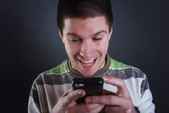 Glückliche Lesung des jungen Mannes eine Mitteilung Stockfotografie