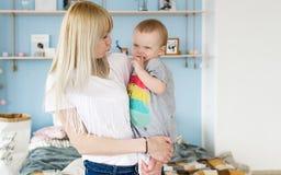 Glückliche liebevolle Familie Junge blonde Mutter, die mit ihrem Baby im Schlafzimmer spielt Lizenzfreies Stockbild