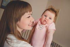 Glückliche liebevolle nette Familie Junge lächelnde Mutter hält ihr neugeborenes Baby Familie zu Hause Kleine Tochter und Mama Lizenzfreie Stockbilder