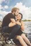 Glückliche liebevolle Paare auf der Flussbank stockbilder