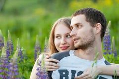 Glückliche liebevolle Paare, die auf dem Gebiet von Lupine umarmen lizenzfreie stockfotografie