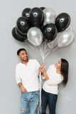 Glückliche liebevolle Paare, die Ballone halten Stockfotografie