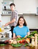 Glückliche liebevolle Paare, die bei Tisch kochen Lizenzfreies Stockfoto