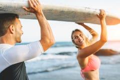 Glückliche liebevolle Paare, die ein Surfbrett halten und - Freunde haben den Spaß surft während Ferien sich schauen lizenzfreie stockfotos