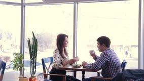 Glückliche liebevolle Paare im lachenden Café, trinkender Tee unter Verwendung der Tablette zum Spaß Erstes Datum stock video