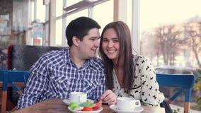 Glückliche liebevolle Paare im lachenden Café, trinkender Tee unter Verwendung der Tablette zum Spaß Erstes Datum stock footage