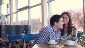 Glückliche liebevolle Paare im lachenden Café, trinkender Tee unter Verwendung der Tablette zum Spaß Erstes Datum stock video footage