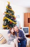 Glückliche liebevolle Paare nähern sich Weihnachtsbaum Stockfoto
