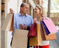 Glückliche Liebhaberfamilie, die Taschen nach dem Einkauf hält Stockbild