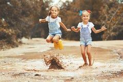 Glückliche lustige Schwestern paart das Kindermädchen, das auf Pfützen in der Unebenheit springt stockbild