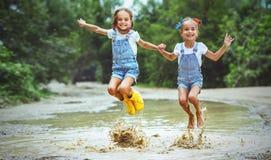 Glückliche lustige Schwestern paart das Kindermädchen, das auf Pfützen in der Unebenheit springt Lizenzfreie Stockbilder