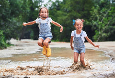 Glückliche lustige Schwestern paart das Kindermädchen, das auf Pfützen in der Unebenheit springt Lizenzfreies Stockbild