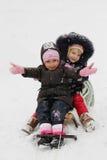 Glückliche Mädchen in den Winterstoffen, die auf Schlitten schieben Stockbilder