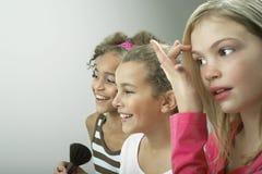 Glückliche Mädchen, die auf Make-up sich setzen Stockbilder