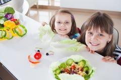 Glückliche Mädchen, die lustige Salatgesichter machen Kochen der vegetarischen Mahlzeit Stockfotos