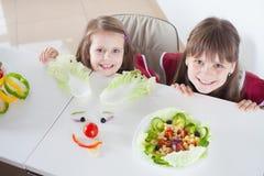 Glückliche Mädchen, die lustige Salatgesichter machen Kochen der vegetarischen Mahlzeit Stockbild