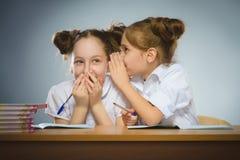 Glückliche Mädchen, die am Schreibtisch auf grauem Hintergrund sitzen Auf schwarzem Hintergrund mit copyspace Stockbilder