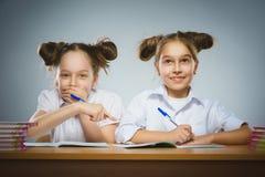Glückliche Mädchen, die am Schreibtisch auf grauem Hintergrund sitzen Auf schwarzem Hintergrund mit copyspace Lizenzfreie Stockfotos